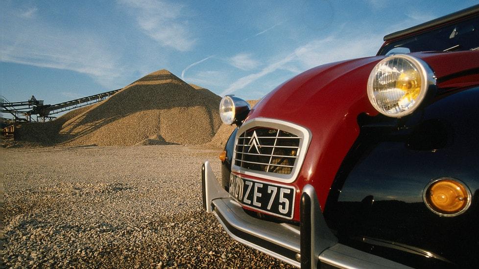 Presentata al Salone dell'auto di Parigi nel 1948, la 2CV, che diverrà uno dei simboli iconici per eccellenza di casa Citroën, ha avuto una genesi lunghissima. Il progetto T.P.I. (auto piccolissima) nasce addirittura nel 1934 e prende definitivamente il via l'anno seguente, dopo la morte di André Citroën, con delle specifiche a dir poco particolari: una vettura che possa trasportare due contadini in zoccoli e 50 kg di patate, o un barilotto di vino, a una velocità massima di 60 km/h e con un consumo di 3 litri per 100 km. Le sospensioni devono permettere l'attraversamento di un campo arato con un paniere di uova senza romperle, e la vettura dovrà essere adatta alla guida di una conduttrice principiante e offrire un confort indiscutibile. Facile da riparare e manutenere, dai costi ridotti e un'ultima raccomandazione: dovrà essere possibile salire e scendere con un cappello in testa. Il progetto, sospeso durante la seconda guerra mondiale, ebbe una svolta decisiva grazie al lavoro sulla carrozzeria (non richiesto) di Flaminio Bertoni e sul motore di Walter Becchia. I due, non lo sapevano, ma stavano creando una leggenda che sarà in produzione ininterrottamente fino al  1990.
